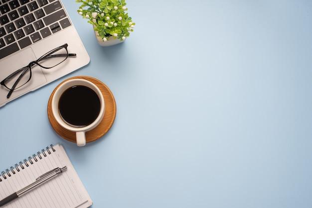 Widok z góry niebieskiego biurka z innym sprzętem do pracy kubkiem do kawy. skopiuj miejsce.