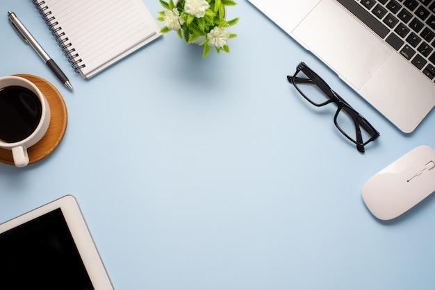 Widok z góry niebieskiego biurka ze sprzętem roboczym umieszczonym w biurze. skopiuj miejsce.