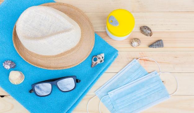 Widok z góry niektórych artykułów plażowych, takich jak ręcznik, czapka i okulary przeciwsłoneczne wraz z parą ochronnych masek na twarz na drewnianej desce. leżał na płasko