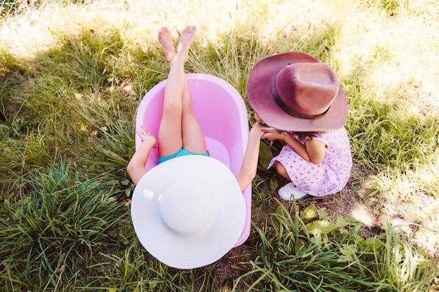 Widok z góry nierozpoznawalne rodzeństwo bawiące się razem na pustym basenie w lecie. małe siostry bawią się w domu podczas wiosennych wakacji. styl życia z dziećmi na wsi.
