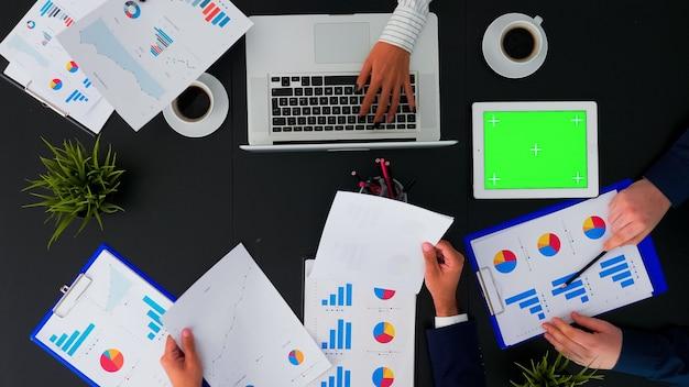 Widok z góry nierozpoznawalnego biznesmena patrzącego na zielony ekran tabletu podczas burzy mózgów w sali konferencyjnej analizującej wykresy ze współpracownikami siedzącymi na stole biurowym