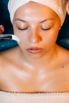 Widok z góry niesamowitej twarzy kobiety opierającej się o łóżko spa z zamkniętymi oczami wykonującej zabieg na twarz kwasem hialuronowym w ośrodku wellness.