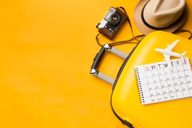 Widok z góry niezbędnych artykułów podróżnych z bagażem i kalendarzem