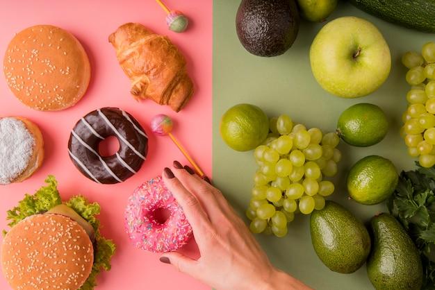 Widok z góry niezdrowe jedzenie kontra zdrowe jedzenie z ręki trzymającej pączek