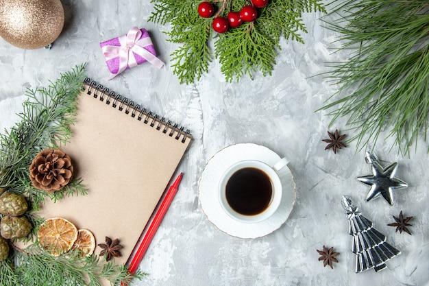 Widok z góry notatnik suszone plasterki cytryny anyż gałęzie sosny czerwony ołówek filiżanka herbaty na szarej powierzchni