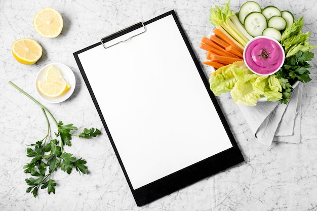 Widok z góry notatnika z talerzem warzyw i cytryny