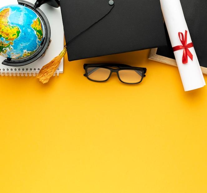 Widok z góry notebooka z akademicką czapką i miejscem na kopię