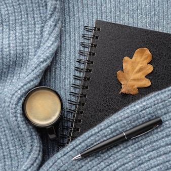 Widok z góry notebooka z jesiennym liściem i filiżanką kawy na swetrze