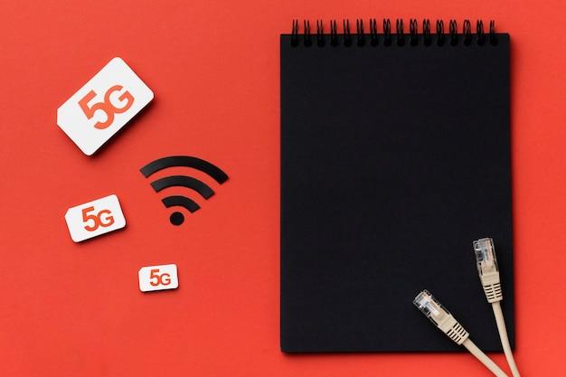 Widok z góry notebooka z kartą sim i kablami ethernet