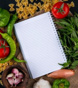 Widok z góry notebooka z surowym makaronem, pomidorami, cebulą, czosnkiem i papryką chili na beżowej serwetce