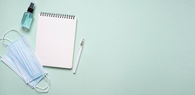 Widok z góry notebooka ze środkiem dezynfekującym do rąk i maskami medycznymi