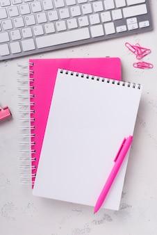 Widok z góry notesów na biurku z spinaczami i długopisem