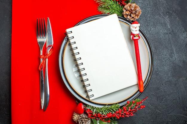 Widok z góry notesu na spirali i długopisu na talerzu z akcesoriami do dekoracji gałązek jodły i sztućców na czerwonej serwetce