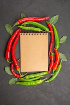 Widok z góry notesu w kręgu czerwonej i zielonej ostrej papryki i płatnych liści na czarnym tle