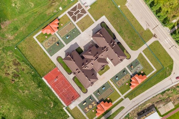 Widok z góry nowego budynku prescool i podwórka z wnękami i zielonymi trawnikami.
