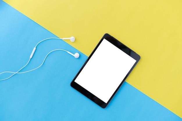 Widok z góry nowoczesne cyfrowe tabletki i białe słuchawki na niebiesko z żółtym kolorem