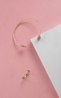 Widok z góry nowoczesne złote bransoletki i pierścionek na białej i różowej powierzchni papieru