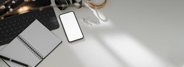 Widok z góry nowoczesnego stołu roboczego ze smartfonem, notebookiem, innymi materiałami eksploatacyjnymi i miejsca na kopię