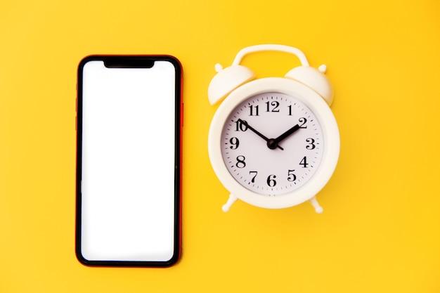 Widok z góry nowoczesny smartfon i biały budzik na niebiesko żółtym
