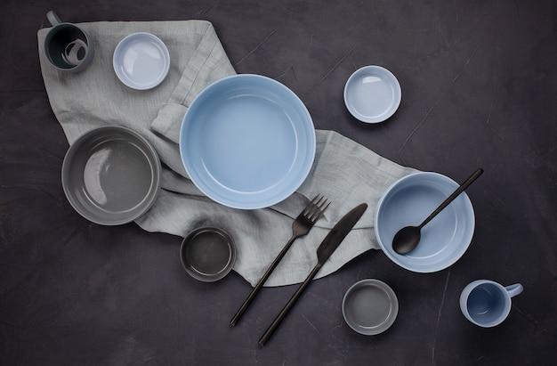 Widok z góry nowoczesnych modnych talerzy w kolorach bleu i szarym. minimalistyczne mieszkanie leżało z zastawą stołową