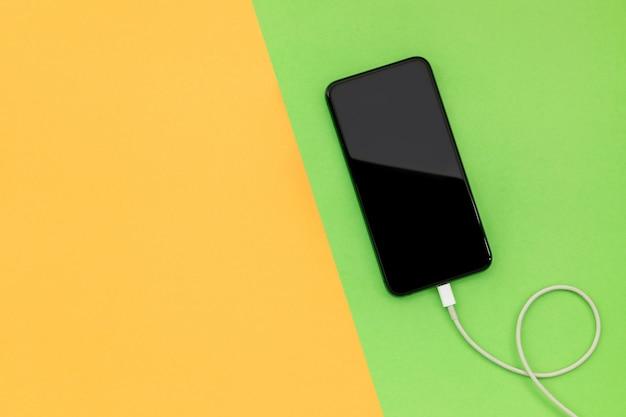 Widok z góry nowy smartfon z białą ładowarką