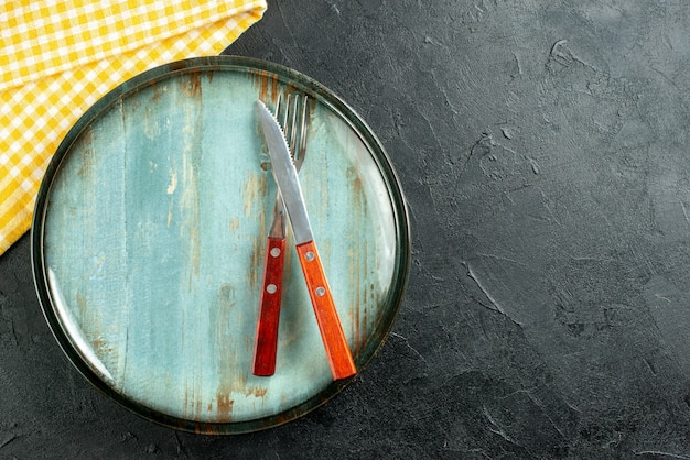 Widok z góry nóż i widelec na talerzu żółta biała serwetka w kratkę na ciemnym podłożu z miejscem kopiowania