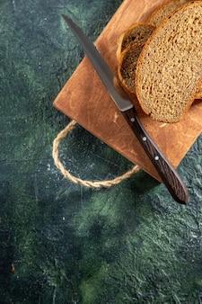 Widok z góry noża do czarnego chleba na brązowej drewnianej desce do krojenia na ciemnej powierzchni