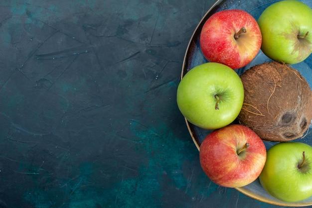 Widok z góry o różnych kompozycjach owocowych jabłka kokosowe i banany na ciemnoniebieskim biurku