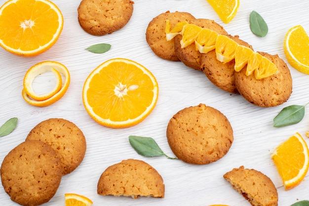 Widok z góry o smaku pomarańczowym ciasteczka ze świeżymi plasterkami pomarańczy na lekkim biurku ciasteczka owocowe cukier herbatnikowy