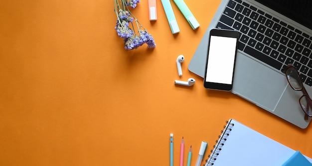 Widok z góry obraz białego pustego ekranu smartfona i laptopa komputerowego zakładającego kolorowe biurko do pracy otoczone kwiatami, długopisami, bezprzewodowymi słuchawkami, ołówkami, okularami i notatnikiem.