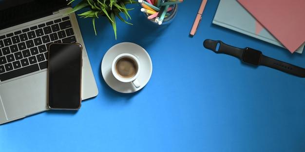 Widok z góry obraz laptopa komputerowego nakładającego kolorowe biurko z filiżanką kawy, roślin doniczkowych, ołówków w szklanym wazonie, smartfona, notatki, smartwatch i notebooka. koncepcja uporządkowanego obszaru roboczego.