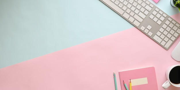 Widok z góry obraz pastelowego koloru stołu roboczego ze stawiającym go sprzętem biurowym. płaska klawiatura, mysz bezprzewodowa, filiżanka kawy, notatnik, roślina doniczkowa i ołówki. urocza koncepcja miejsca pracy.