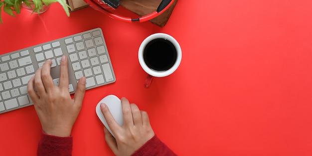 Widok z góry obraz rąk wpisujących na klawiaturze bezprzewodowej i za pomocą myszy bezprzewodowej na czerwonym biurku otoczonym filiżanką kawy, bezprzewodowymi słuchawkami, starymi książkami i rośliną doniczkową. koncepcja uporządkowanego obszaru roboczego.