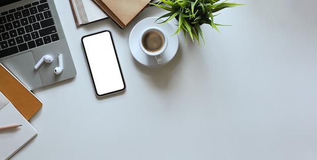 Widok z góry obraz smartfona z białym pustym ekranem stawiającym na białym biurku i otoczony komputerowym laptopem, rośliną doniczkową, notatnikiem, pamiętnikiem, filiżanką kawy, ołówkiem i bezprzewodową słuchawką.