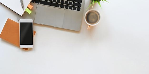 Widok z góry obraz smartfona z czarnym pustym ekranem, filiżanką kawy, laptopem komputerowym, rośliną doniczkową, notatką, pamiętnikiem i piórem układającymi na białym biurku. koncepcja uporządkowanego obszaru roboczego.