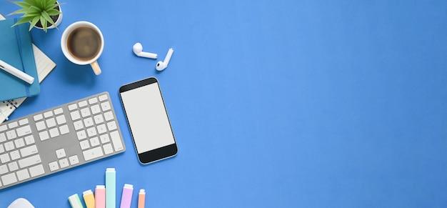Widok z góry obraz stołu roboczego z nakładanymi akcesoriami. biały pusty ekran smartfona, filiżanka kawy, bezprzewodowe słuchawki, notatnik, długopis i klawiatura bezprzewodowa leżały płasko na niebieskiej przestrzeni.