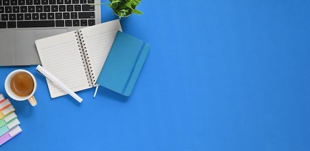 Widok z góry obraz stołu roboczego z nakładanymi akcesoriami. komputerowy laptop, filiżanka kawy, notatnik, długopis i pisaki leżały płasko na niebieskiej przestrzeni.