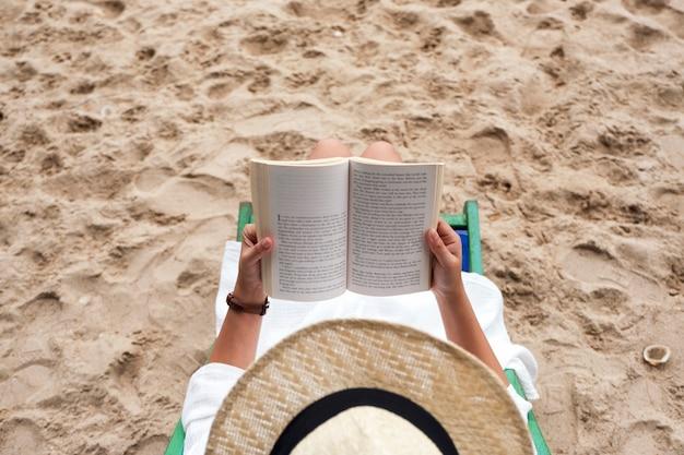 Widok z góry obrazu pięknej kobiety leżącej i czytającej książkę na leżaku z uczuciem relaksu
