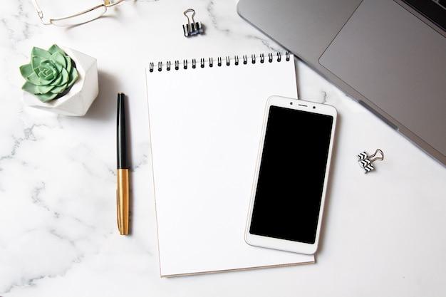 Widok z góry obszar roboczy z makiety notesu, smartfona, laptopa na marmurowym tle