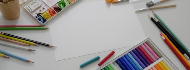Widok z góry obszaru roboczego artysty z papieru do szkicu, pasteli olejnych, narzędzi do malowania i przestrzeni kopii