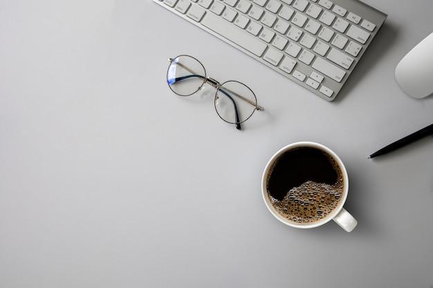 Widok z góry obszaru roboczego biurka z filiżanką kawy, klawiaturą i harmonogramem pracy na tle białego stołu.