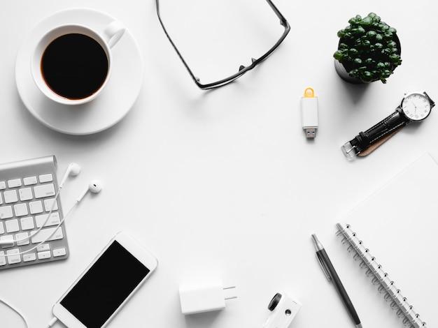 Widok z góry obszaru roboczego biurka z filiżanką kawy, notatnik, roślina z tworzywa sztucznego, tablet graficzny na białym tle z miejsca kopiowania, grafik, koncepcja kreatywnego projektanta.