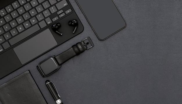 Widok z góry obszaru roboczego w kolorze czarnym z klawiaturą komputerową, smartwatchem, smartfonem, słuchawkami, długopisem i książką, miejsce na kopię.