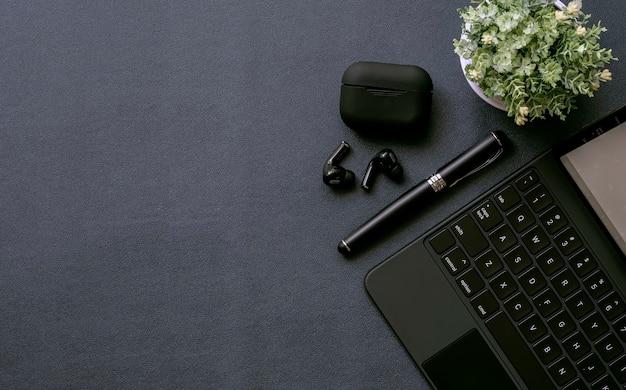 Widok z góry obszaru roboczego w kolorze czarnym z komputerem typu tablet, długopis, słuchawki i roślina doniczkowa na tle czarnej skóry.