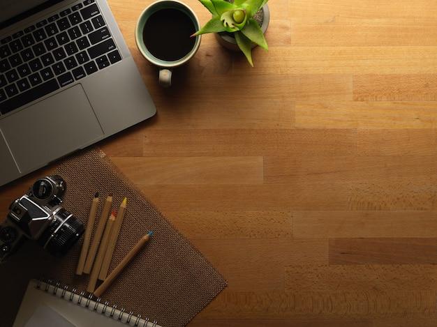 Widok z góry obszaru roboczego z laptopem, aparatem, papeterią i miejscem na kopię na drewnianym biurku