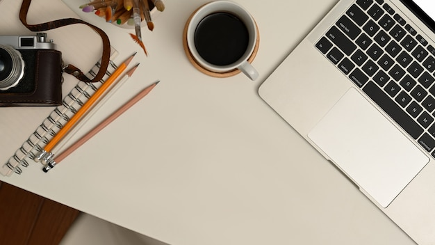 Widok z góry obszaru roboczego z laptopem, filiżanką kawy, papeterią