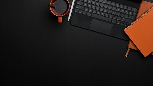 Widok z góry obszaru roboczego z laptopem, notebookami, filiżanką kawy i miejscem na kopię w biurze