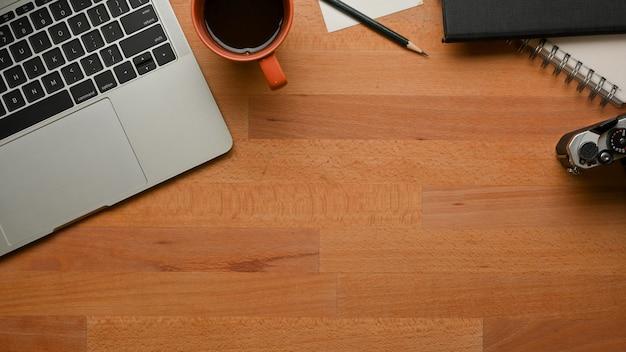 Widok z góry obszaru roboczego z laptopem, papeterią, kubkiem do kawy i miejscem na kopię w pokoju biurowym