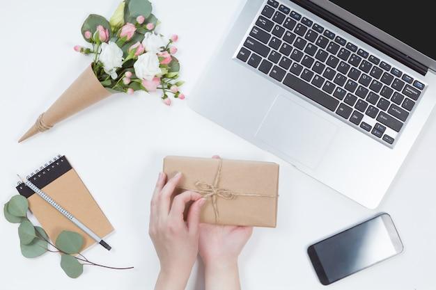 Widok z góry obszaru roboczego z laptopem, ręce kobiety z pudełko, notatnik, telefon komórkowy