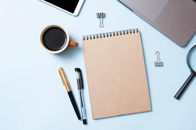 Widok z góry obszaru roboczego z makiety notesu, kawy, laptopa na niebieskim tle